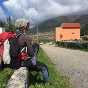Charlotta sitter på en mur utmed grusvägen och fixar med skosnörena. Ryggsäck på ryggen, ett hus i bakgrunden med ett berg som fond.